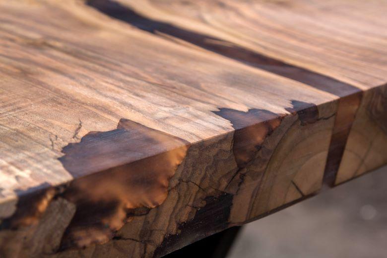 Ästhetischer Holztisch, dessen Risse professionell mit hochwertigem Epoxidharz gefüllt worden sind