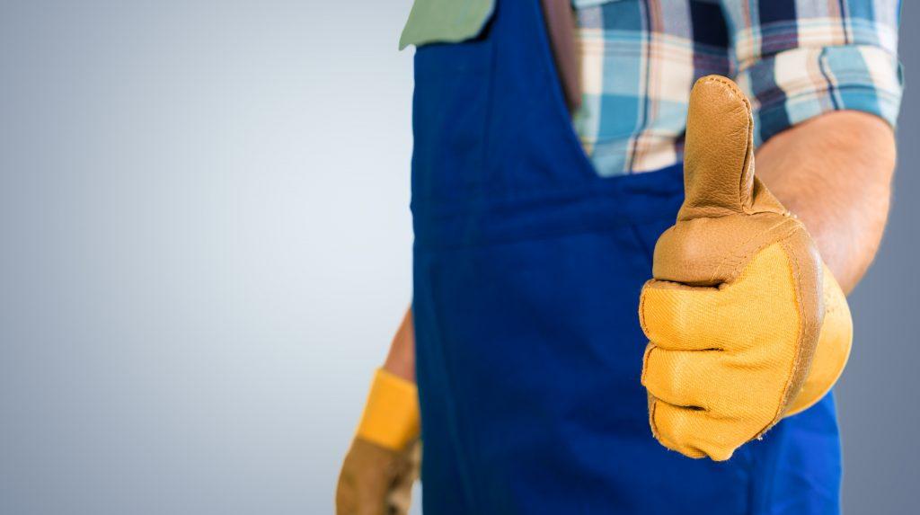 Handwerker mit Handschuhen und Daumen noch kurz vor dem Epoxidharz-entfernen